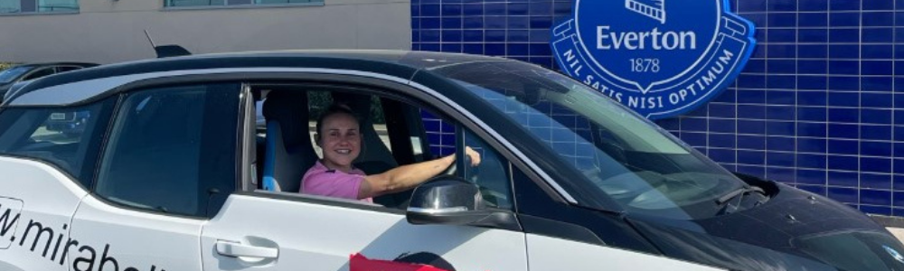 Everton dynamo Izzy Christiansen pictured with BMW i3 electric car provided by EVision